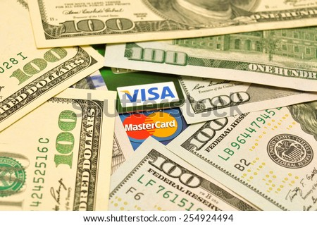 POLTAVA, UKRAINE - JANUARY 24, 2015: Photo of Visa and Mastercard credit card with USA dollars bills - stock photo