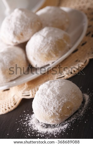 polvoron cookies with pecans and powdered sugar macro on the table. vertical