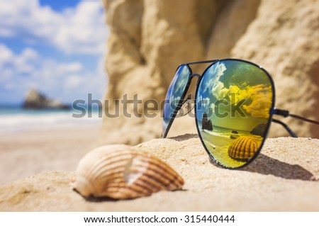 Poly-color sunglasses, reflecting the ocean and a shell on a sandy, tropical beach - stock photo