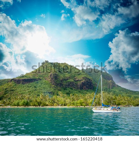 Polynesia Island with pristine waters and blue sky. - stock photo