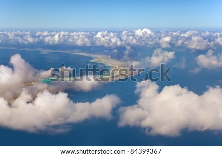 Polynesia. The atoll ring at ocean is visible through clouds. Aerial view - stock photo