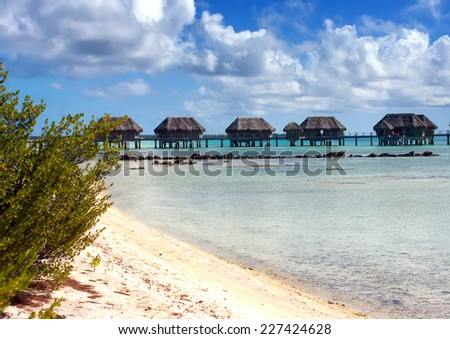 Polynesian landscape -small houses on water. - stock photo