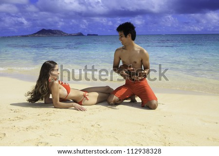 polynesian man shows girl how to play ukulele on the beach in hawaii - stock photo