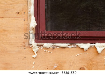 Polyurethane foam fills in gap at window just inserted in opening - stock photo