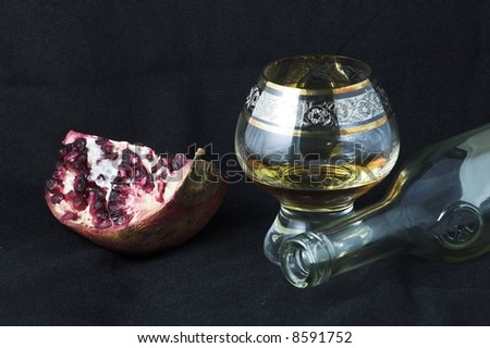 Pomegranate and cognac glass on a black background - food joy