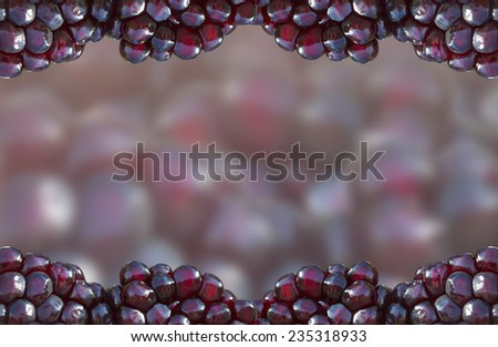 Pomegranate aril (seed) background with isolated focused seeds forming a frame around blurred background