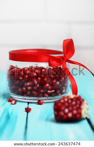 Pomegranate berries in a glass jar with a red bow - stock photo