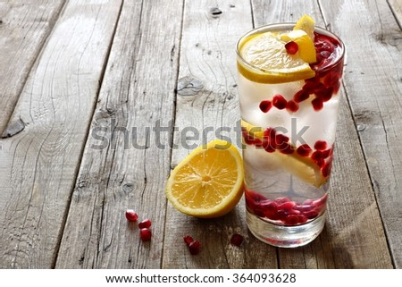 Pomegranate detox water in a glass against a rustic wood background - stock photo