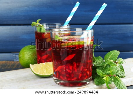 Pomegranate drink in glasses with slices of lime and mint on color wooden background - stock photo