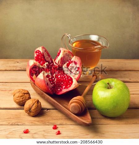Pomegranate for Jewish New Year celebration. Focus on pomegranate. - stock photo