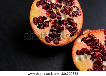 Pomegranate fruit cut in half on a dark background, showing red seeds, flatly