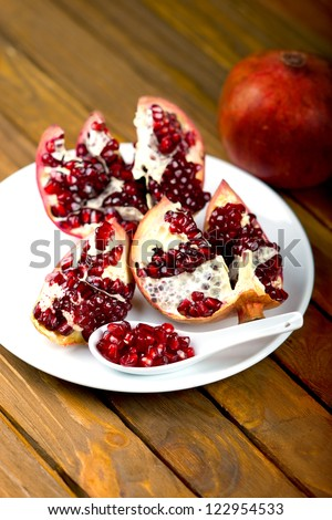 Pomegranate fruit on the table, sliced ??pomegranate on a plate, peel a pomegranate,