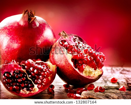 Pomegranate fruit. Pomegranates over Red Background. Organic Bio fruits - stock photo