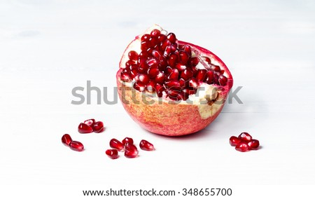 Pomegranate fruit, seeds, kiwi and leafs on white textured wooden board - stock photo