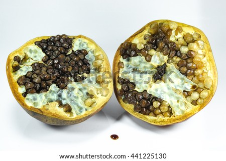 Pomegranate fruit that can not be eaten because it is spoiled on white background - stock photo