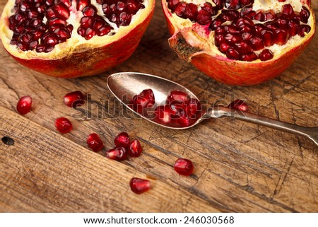 Pomegranate fruits and seeds with silver teaspoon in the front, wooden background - stock photo