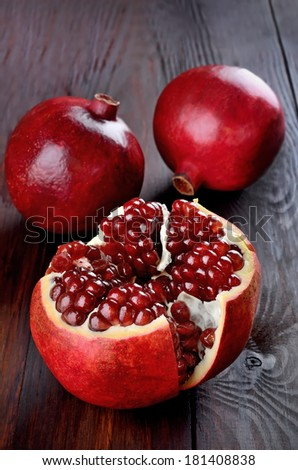 Pomegranate fruits on wooden table - stock photo