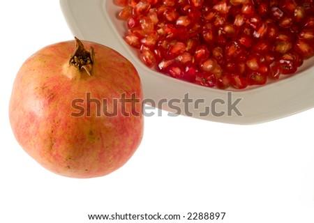 Pomegranate grains on dish and whole pomegranate - stock photo