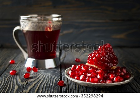 Pomegranate juice and pomegranate on wooden table - stock photo