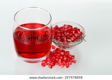Pomegranate juice in a glass and ripe pomegranate seeds in glass bowl.