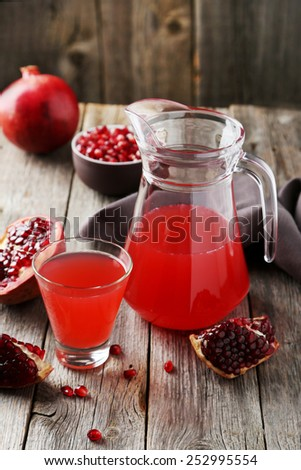 Pomegranate juice in glass and pitcher on grey wooden background - stock photo