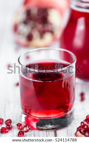 Pomegranate juice on a vintage background as detailed close-up shot (selective focus)