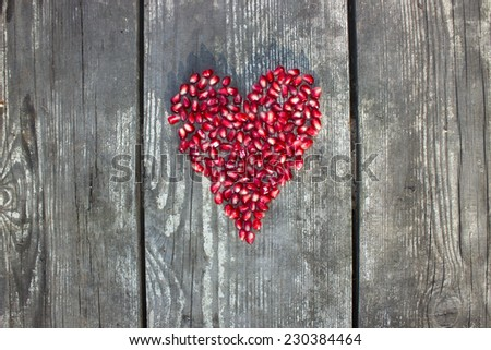 Pomegranate macro seeds in heart shape on grey wooden background - stock photo