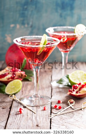 Pomegranate martini with slices of lime and pomegranate seeds - stock photo