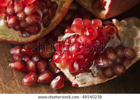 Pomegranate on wooden surface broken open with seeds scattered - stock photo