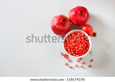pomegranate on wooden table, and fresh pomegrante seed in bowl  - top view. - stock photo