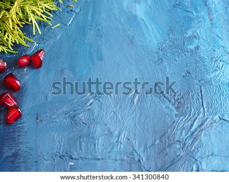 Pomegranate seeds and a branch of thuja on dark blue background with snow effect texture, copy space - stock photo