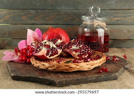Pomegranate seeds on wicker tray and jar of juice on wooden background