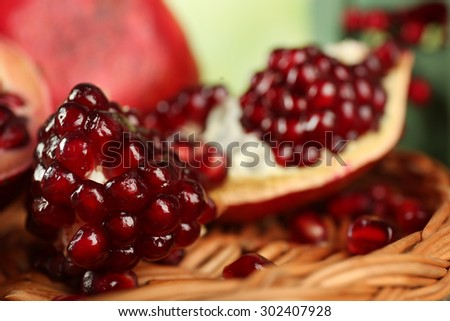 Pomegranate seeds on wicker tray, closeup