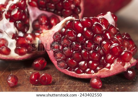 Pomegranate sitting on a dark brown, wooden cutting board. The pomegranate is cut open, with several seeds falling out