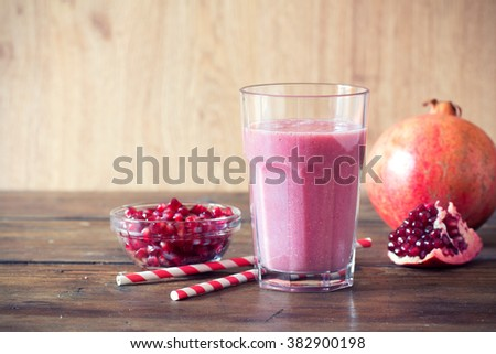 pomegranate smoothie on wooden background - stock photo