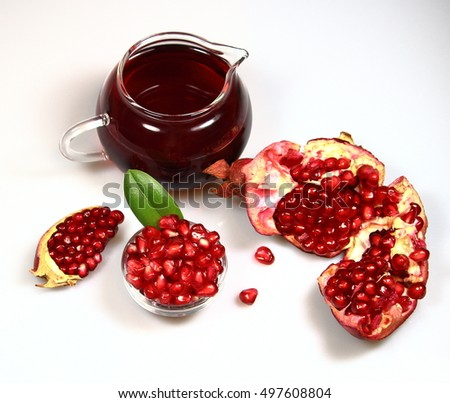 pomegranate with a green leaf in a  plate and garnet juice