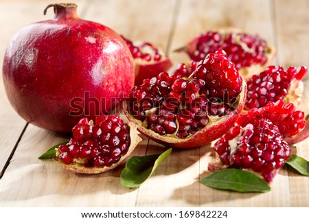 pomegranate with leafs on wooden table - stock photo