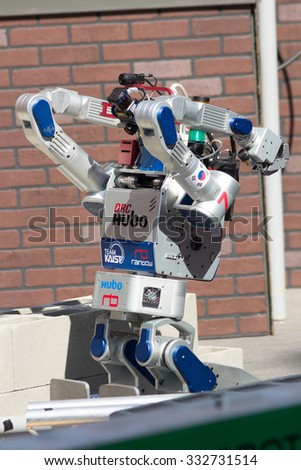 POMONA, CA - JUNE 6: Team KAIST's DRC-Hubo robot successfully rolls through rubble at the DARPA Robotics Challenge in Pomona, CA on June 6, 2015. The Korean robot went on to win the competition. - stock photo