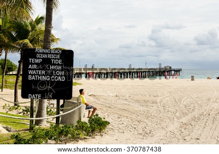 POMPANO BEACH, FL - JANUARY 8, 2016: Fishing pier and weather information board photographed on January 8, 2016 in Pompano beach, Florida - stock photo