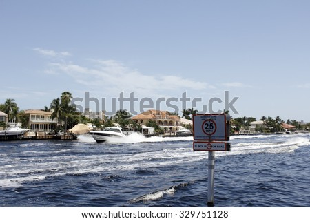 Pompano Beach, FL, USA - July 4, 2014: Boats travel in the intracoastal waterway creating good sized waves on this sunny day with a Manatee Zone 25 miles per hour sign closeup. Many boats traveling - stock photo