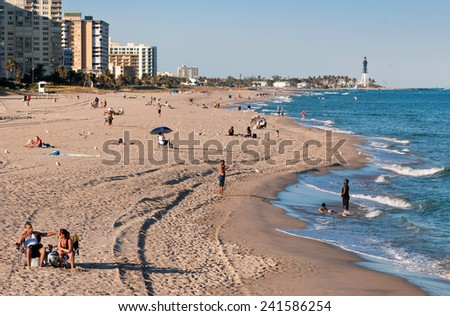 POMPANO BEACH, FLORIDA - JANUARY 29: Tourists enjoying the beach and view at the Hillsboro Inlet lighthouse at Pompano Beach in Florida on January 29, 2011.  - stock photo