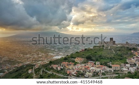 Pompei and Vesuvius landscape close to Napoli in Italy. Cityscape with ancient castle in foreground and active volcano in background in a cloudy spring day at sunset