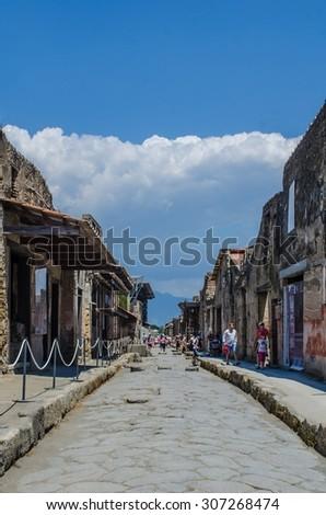 POMPEI, ITALY, JUNE 28, 2014: people are walking through the ruins of former italian city pompeii near naples. - stock photo