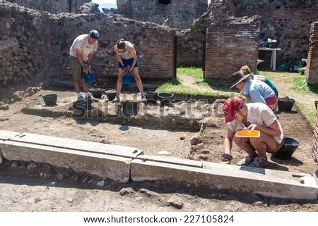 POMPEII, ITALY - JULY 27: Archelogists work at antique ruins of town Pompeii, Italy on July 27, 2014. Pompeii was destroyed and buried with ash and pumice after Vesuvius eruption in 79 AD. - stock photo