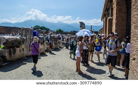 POMPEII, ITALY, JUNE 29, 2014: people are walking through ruins of the historical city of pompeii. - stock photo