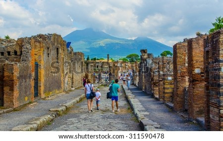 POMPEII, ITALY, JUNE 27, 2014: people are walking through ruins of the historical city of pompeii. - stock photo