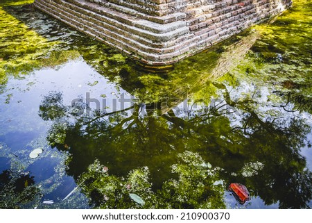 pond, building in ruins on a green swamp with water - stock photo