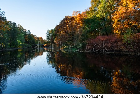 Pond in the autumn park with trees reflected in it  - stock photo