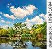 pond with lush tropical plants over cloudy blue sky. luxury resort - stock photo