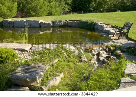 Pond with water falls and bench
